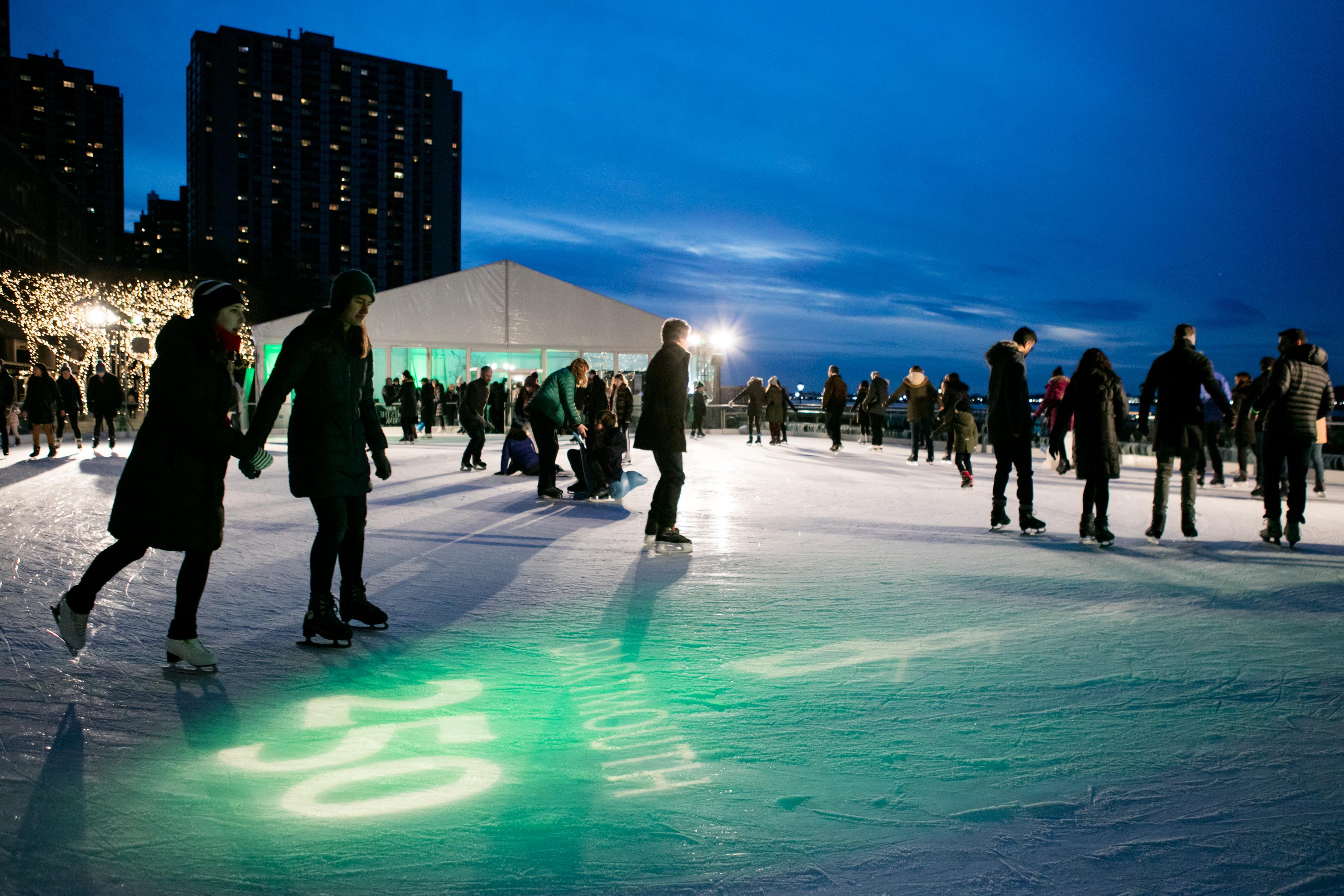 Dartmouth alumni and friends skate under a green-lit skyline