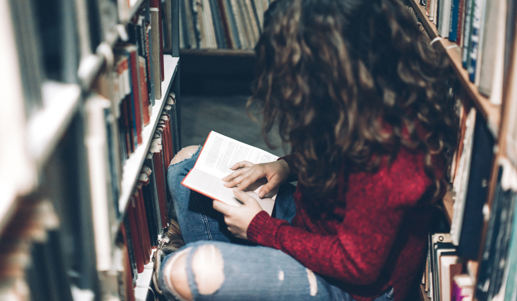 Student reading in stacks