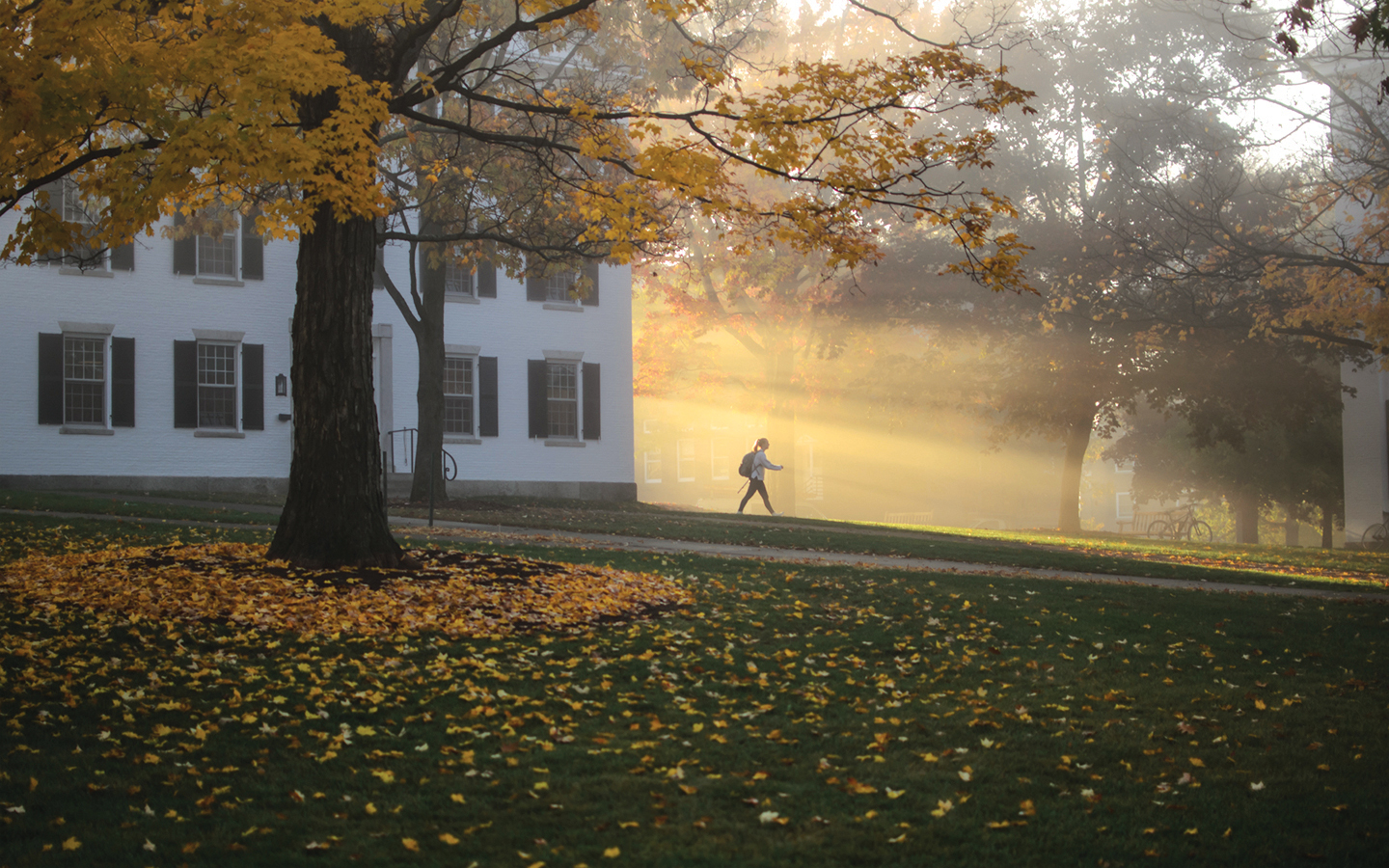 young woman walking in morning sunlight from Dartmouth Hall