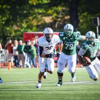 Dartmouth football players run down the field