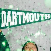 Student holding Dartmouth banner as green glitter falls