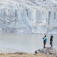 Students stand on a glacier while conducting research in the Arctic