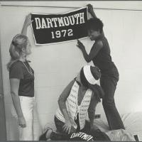 Women hanging a Dartmouth banner in their dorm room