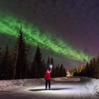 Someone standing outside with a flashlight at night under the northern lights.
