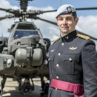 "Captain William ""Zack"" Zehner '09 stands in front of an Apache helicopter"