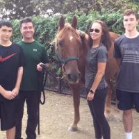 The Burke family stands with a horse.