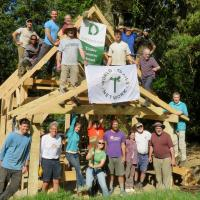 The crew poses for a photo alongside the finished timber frame.