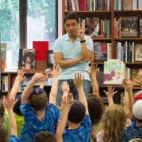 Minh Lê '01 surrounded by young readers.
